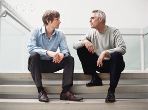 Two Men Sitting on Stairs Talking